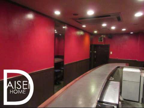 なだらかな円形をかたどったカウンターと赤い壁が印象的なお店です。